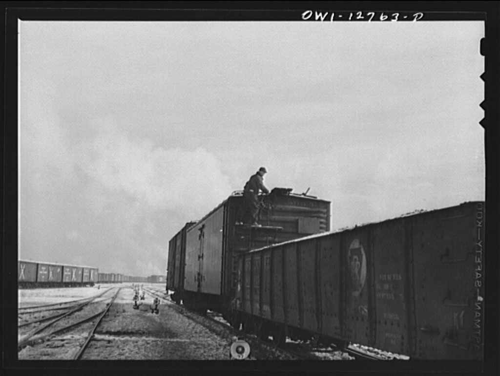 Chicago, Illinois. Switching cars in one of the Chicago and Northwestern Railroad classification yards. The switch man is braking the last two cars