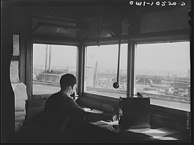 Chicago, Illinois. The engine foreman controls the cars coming over the hump at an Illinois Central Railroad yard and checks them against his list