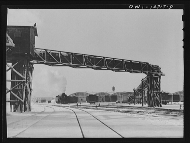 Chicago, Illinois. Train pulling out of a freight house at a Chicago and Northwestern Railroad yard. The wooden trestle is part of a long chain belt used to carry blocks of ice from the ice house to the freight house