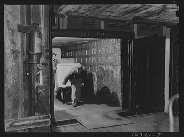Chicago, Illinois. Unloading a truck for shipment of goods by rail in the freight house at a Chicago and Northwestern Railroad yard