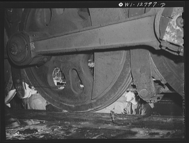 Chicago, Illinois. Working on the underside of a locomotive in a pit at the roundhouse at the Chicago and Northwestern Railroad yard