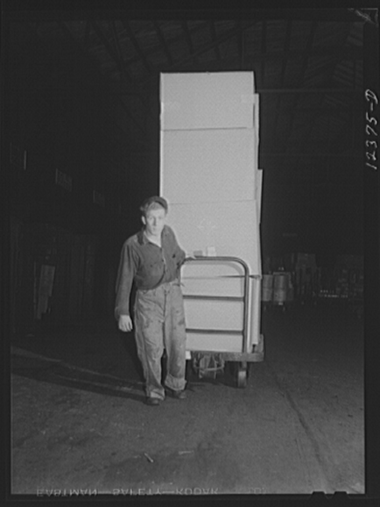 Chicago, Illinois. Workman hauling a hand truck loaded with goods at a freight house at a Chicago and Northwestern Railroad yard. The men are paid according to the tonnage handled per day
