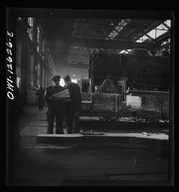 Chicago, Illinois. Workmen studying blueprints in the locomotive shops of the Chicago and Northwestern Railroad. The long bar on the ground is to be made into part of a locomotive frame