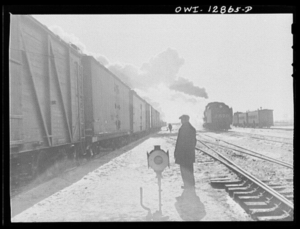 Chicago, Illinois. Yardmaster watching a train pulling out of one of the Chicago and Northwestern Railroad