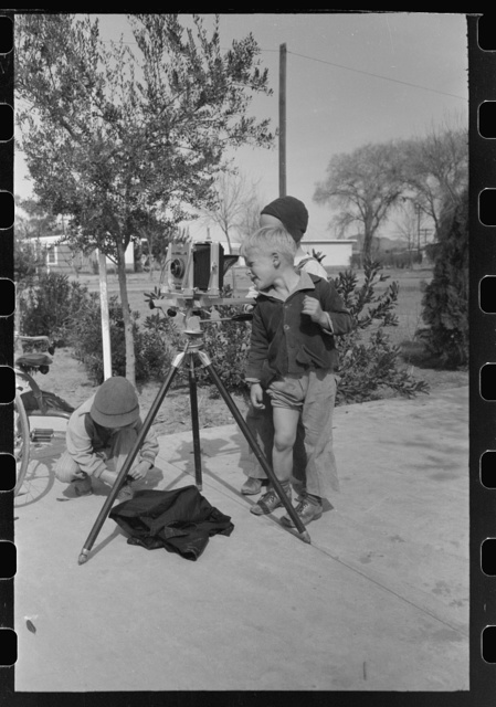 Children at the FSA (Farm Security Administration) Camelback Farms inspect the photographer's camera, Phoenix, Arizona