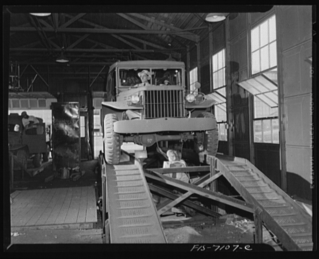 Chrysler Corporation. Dodge truck plant. Detroit, Michigan (vicinity). War worker checking lubrication as another Dodge army truck nears delivery to the Army