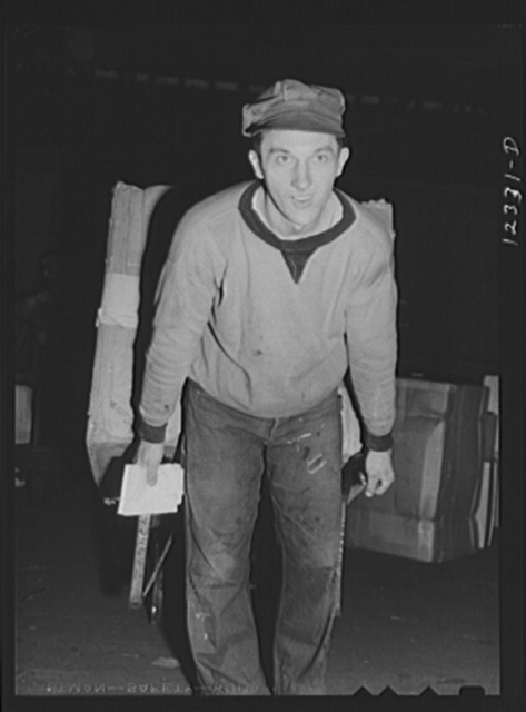 Cihcago, Illinois. Workman in the freight house at the Chicago and Northwestern Railroad yards, pulling a hand truck