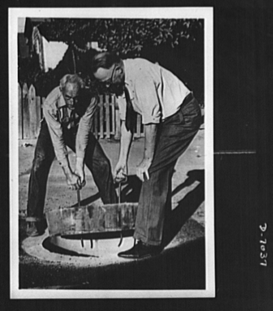 Conservation. Wooden manhole covers. Lifting a wooden manhole cover into place is Colonel Carl H. Reeves, superintendent of the Los Angeles County, California, Maintenance Department. Treated to resist termites and decay, each wooden cover saves 500 pounds of metal. It may be manufactured without the use of extensive fabricating equipment. A War Production Board (WPB) order prohibits the use of iron and steel for manhole covers