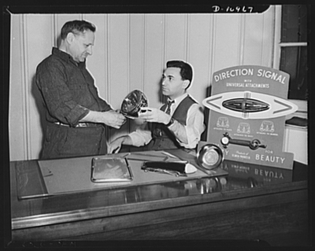 Conversion (auto accessory plant). Benjamin Lapides (right) and his father Leon Lapides, owners of the firm shown inspecting the line of automobile accessories made by the firm prior to ninety percent conversion to war production