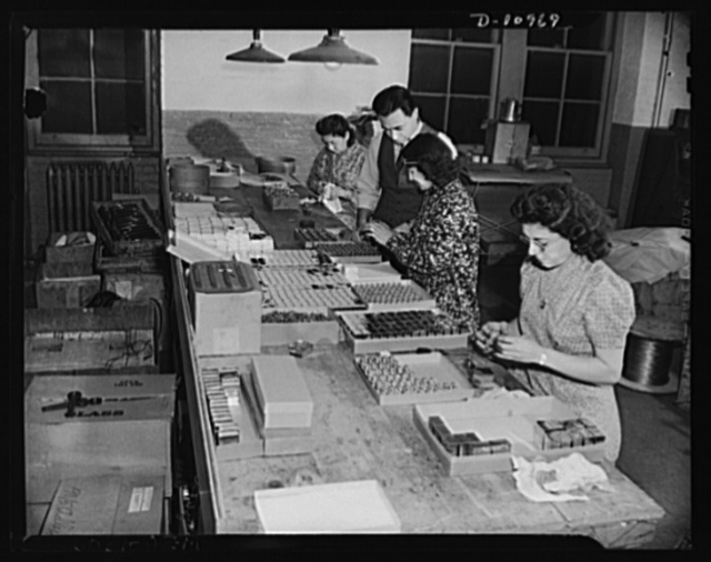 Conversion (auto accessory plant). Photo shows girl workers at a New York City plant assembling field sterilizers for the United States Army Medical Corps.  Sol Lapides, partner in the firm inspects work. This firm formerly engaged in the manufacture of automobile accessories. Since converted ninety percent to war production