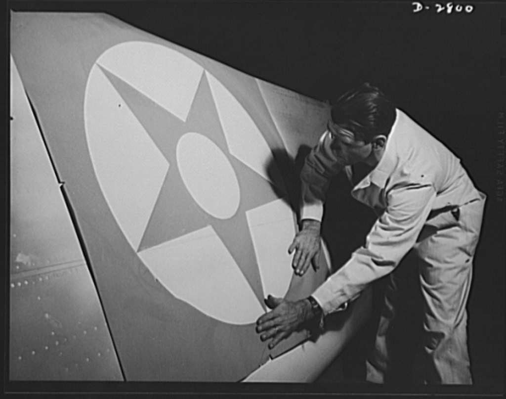 Conversion. Auto body plant. He's marking this wing with the colors of victory--red, white and blue. Stencil being applied to wing tip in one of America's automobile body plants newly converted to airplane Production. Briggs Manufacturing Company, Detroit, Michigan