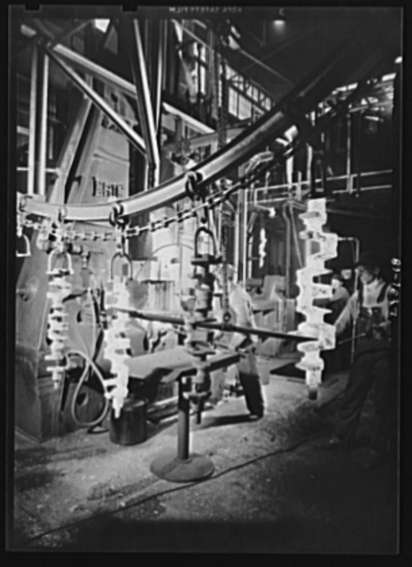 Conversion. Auto engines to military truck engines. Forging weapons for war. Crankshafts for military trucks are shaped on a huge Erie forging press served by an endless chain conveyor. Site: a Midwest auto plant converted to war production