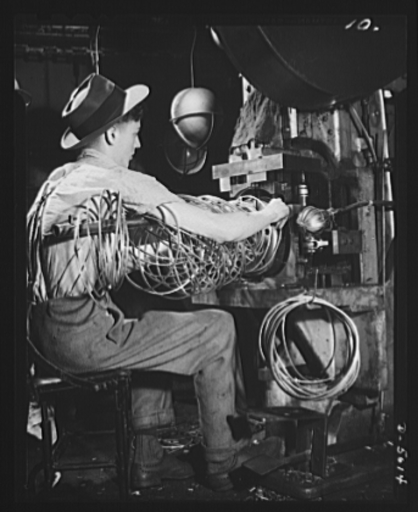 Conversion. Auto radiators to army helmets. The rim of an army helmet is formed on a press from steel rod. Finished rims are shown on the hook below the operator's right hand. The helmets are made in an Eastern plant converted by retooling from the production of automobile radiators. McCool Radiator Company, Detroit, Michigan