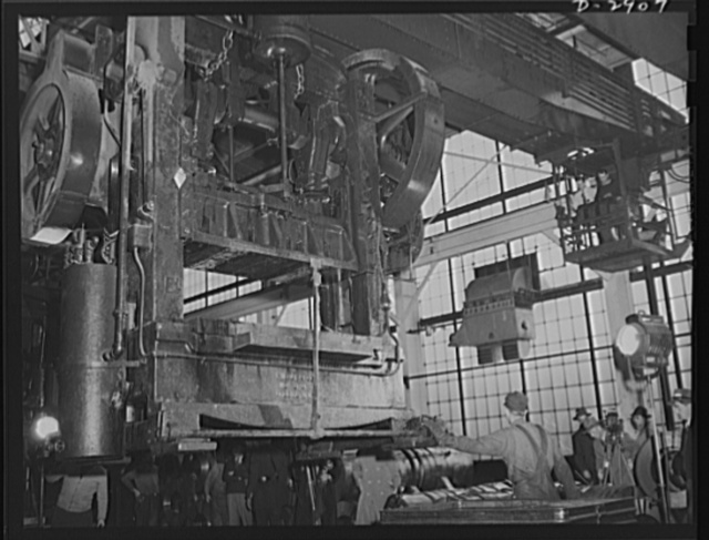 Conversion. Automobile plant. A giant overhead crane moves a 6D Bliss press, weighing seventeen tons, from a plant being entirely cleared for outright conversion to armament Production. When set up in another of the buildings of a big automobile factory, this press will form door trim panels of 4 x 4 and 6 x 6 army trucks. Chevrolet Motor, Detroit, Michigan