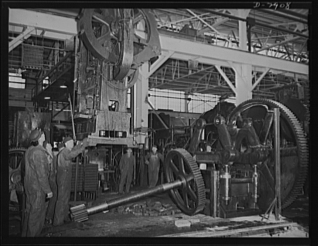 Conversion. Automobile plant. A seventeen-ton 6D Bliss press is lowered by overhead crane to the location at which it will produce door trim panels for 4 x 4 and 6 x 6 Army trucks. The press was taken from another of the plant buildings that is being entirely cleared for conversion to other war production. Chevrolet Motors, Detroit, Michigan