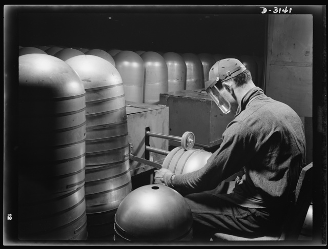 Conversion. Beverage containers to aviation oxygen cylinders. After the circumferential straps are welded to the cylindrical portion, in the metal division of a large Eastern rubber factory, rough edges and accumulated weld scale are removed by a skilled workman. The twin rotary brushes, shown above, do their work on the inside and outside of the cylinder in the same operation. This process is required in the manufacture of shatterproof oxygen cylinders for high altitude flying. Firestone, Akron, Ohio