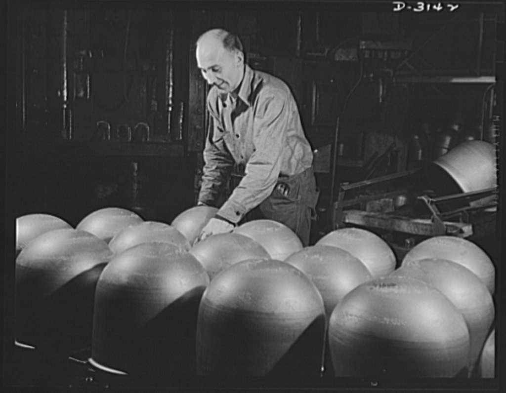 Conversion. Beverage containers to aviation oxygen cylinders. After they are stamped on the huge toggle press in the metal division of a large rubber factory, these cylindrical domes which make up half of a shatterproof oxygen cylinder, are placed on a large conveyor where they are carried to workmen who will apply the circumferential and longitudinal straps. Cylinders are used for high altitude flying as a source of oxygen. Firestone, Akron, Ohio