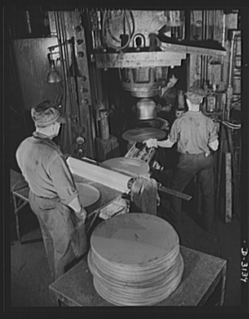 Conversion. Beverage containers to aviation oxygen cylinders. The first step in the manufacture of high-altitude-flying shatterproof oxygen cylinders in the metal department of a large rubber factory is the forming or stamping of the shell. Stainless steel sheets are blanked or cut into discs(left foreground). Before stamping, these discs are drawn through rolls where a drawing compound is added to both sides to facilitate the forming of the shell. The 750-ton toggle press, shown above, forms a half cylinder in one powerful stroke. Once the half cylinder is formed, it is trimmed and the value-fitting hole is punched into the spherical dome. A cleaning operation later removes the drawing compound. The cylinder halves are now ready for the various welding operations. Firestone, Akron, Ohio