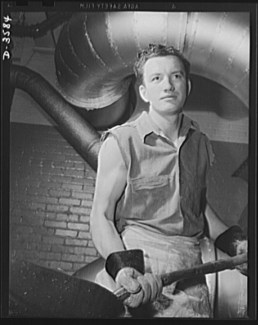 Conversion. Cash registers to gun magazines. A husky worker in a plant that used to make cash registers is kept busy collecting brass scrap from the production of shell fuses and returning it to the factory. Naional Cash Register Company, Dayton, Ohio