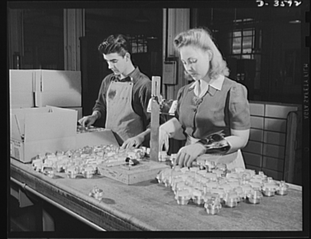 Conversion. Cash registers to gun magazines. Women work side by side with men to smash the Axis. Arming test of M-48 fuse bodies part of the routine inspection of shell parts at a former cash register factory now engaged in war production. National Cash Register Company, Dayton, Ohio