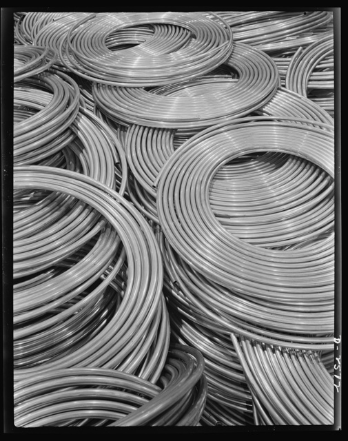Conversion. Copper and brass processing. Coils of copper water tube. Large quantities of copper tube are needed by our Army and Navy, and vital industries. The smaller sizes are used for oil lines on equipment producing defense products and for fuel lines on tanks and other mechanized equipment. Single lengths up to sixty feet are coiled for convenience in handling and shipping. Chase Copper and Brass Company, Euclid, Ohio