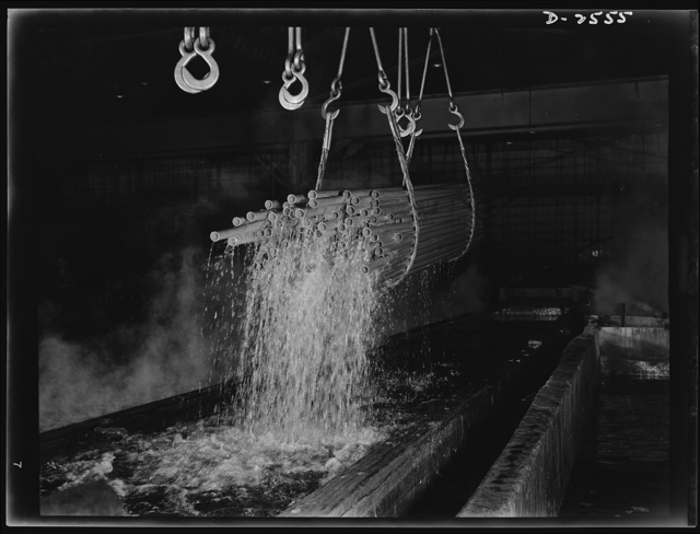 """Conversion. Copper and brass processing. Pickling lengths of copper water tube in a brass and copper mill. After annealing, or softening by heat to reduce brittleness and allow further drawing, tubes are """"pickled"""" in a sulphuric acid solution to remove oxide and scale that result from the anneal. Bundles of the tubes are picked up by electric cranes and transported from the pickle to a rinse bath of water. The tubes are then returned to the drawbench for re-drawing down to smaller diameters. Chase Copper and Brass Company, Euclid, Ohio"""