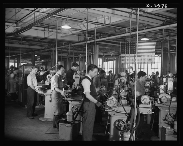 Conversion. Electric shaver plant. This New England whose normal product is electric dry shavers is now turning out parts for machine tools which will find their place in the war production effort. This bank of Norton grinders which formerly ground motor shafts are now grinding small parts for tools. Tolerances on the war work are only .002 inches whereas the former work demanded much closer tolerances up to .0002 inches. The conversion was accomplished by putting on new grinding wheels, by minor changes in the head and by increasing the feed of the cutting solution. Schick Inc., Stamford, Connecticut