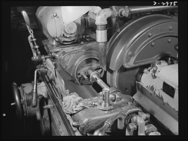 Conversion. Electric shaver plant. This Norton type C six-inch semi-automatic cylindrical grinder in a New England plant used to grind motor shafts for the firm's normal production of electric dry shavers. It is now grinding spring collets which are used in turning machines to hold the work being turned. Such machines are vitally needed for the war production effort. The conversion of the machine was accomplished by replacing the one-inch vitrified aluminum oxide wheel shown here with a three-inch wheel and by enlarging the feed of the cutting solution. Tolerances on this war work are only .002 inches as compared with the tolerances on the normal production of .0002 inches (see pix #D-2974). Schick Inc., Stamford, Connecticut