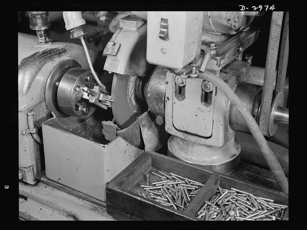 Conversion. Electric shaver plant. This Norton type C six-inch semi-automatic cylindrical grinder in a New England plant normally turns out these motor shafts for the firm's electric shavers. It has since been converted to the grinding of spring collets that are used in machine tools being produced to aid the war production effort. The conversion was easily accomplished by replacing the one-inch vitrified aluminum oxide wheel shown here with a three-inch wheel and by enlarging the feed of grinding solution. In this operation normal tolerance is desired (see pix #D-2975). Schick Inc., Stamford, Connecticut
