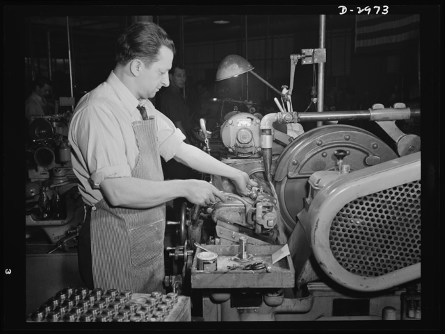 Conversion. Electric shaver plant. This worker in a New England plant that normally produces electric dry shavers is now busy turning out spring collets for machine tools to be used in war production. On this Norton type C six-inch semi-automatic cylindrical grinder, he used to turn out rotor shafts for the motor of the shaver. To convert his machine to the larger grinding job, it was necessary only to exchange the normal one-inch vitrified aluminum oxide wheel for a three-inch wheel and to increase the feed of the cooling solution. This worker was used to working to a tolerance of .0002 inches on the motor shafts so he finds it simple to attain the comparatively rough tolerance of .002 inches required on this war work. Schick Inc., Stamford, Connecticut