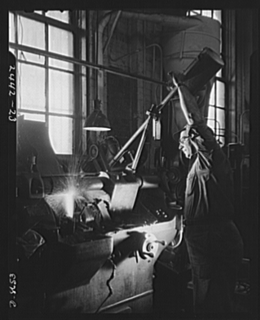 Conversion. Farm implements to gun parts. A grinding operation is performed on a Bofors gun slide in a converted Midwestern farm implement plant which is also making marine steam cargo winches for the Maritime Commission