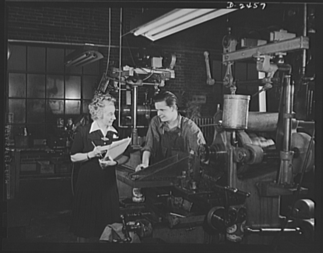 Conversion. Floor waxer plant. A modern Molly Pitcher of the machine, this secretary-treasurer of a small Eastern manufacturing company knows as much about drills and lathes as the oldest employee around the place. And it was in part through her foresight and initiative that this floor waxer plant was converted to war production. She's shown here with a youthful worker who is operating one of the recently converted machines. Floorola Products Inc., York, Pennsylvania