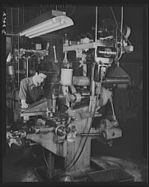 Conversion. Floor waxer plant. Now making machine gun cover plates, this machine was converted from a line shaft drive to motor drive when a small Eastern manufacturing company converted its product from floor waxers to small parts for war equipment. Unable to purchase new equipment for his defense work, the owner bought second-hand equipment and remodelled it. Delivery of first orders was made thirty days after contract, an amazingly short time considering that conversion of the machinery took two weeks of it. Floorola Products Inc., York, Pennsylvania