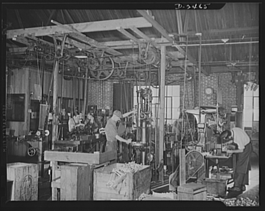Conversion. Floor waxer plant. These twenty-year-old lathes are producing equipment for Uncle Sam's armed forces twenty-two hours a day. Alive to the possibilities of converting old equipment to defense usage, the owner of this small Eastern factory bought and remodelled old equipment which is proving its mettle in 1942. Note overhead power-driven machinery. Floorola Products Inc., York, Pennsylvania