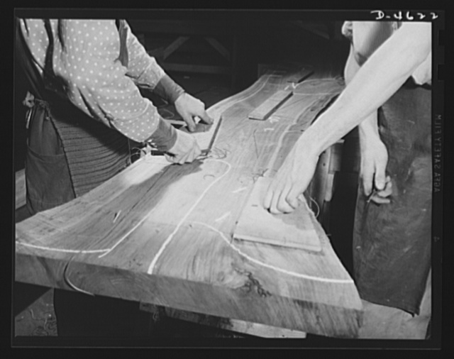 "Conversion. Flooring to gunstocks. Stocks for Army rifles. A large walnut slab, known as a flitch, is marked for the cutting out of sound planes for gunstocks. Light chalk marks indicate defects. Black marks are the outlines to which selected sections for ""rifle furniture"" will be cut. Because of knots, swirls, twisted grain and other faults, only a small percentage of the flitch can be used. Louisville, Kentucky"