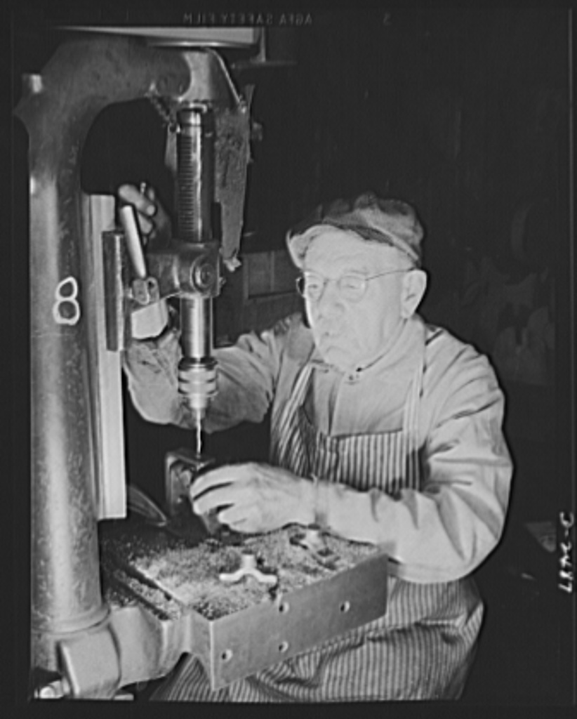Conversion. Food machinery plant. Back to aid in his country's war effort is Phineas Davenport Allen, seventy-eight-year-old mechanic who worked on steering riggings for submarines during World War I. Today he is employed by a New England company, whose normal peacetime product is cube steak machinery. The drill press he operates was a valuable part of the company's peacetime equipment, is even more valuable today in the speeding of work on war subcontracts. Here Allen is drilling bearing caps for cube steak machines. Cube Steak Machine Company, Boston, Massachusetts