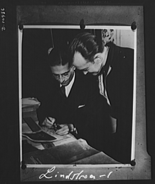 Conversion. From garage to defense workshop. At left, George W. Bocdanoffy, vice president of the machine shop company explains a job to John Lindstrom of Howe Company. Formerly an employee, Lindstrom now is his own boss doing subcontracting for his former boss in a small machine shop set up in the garage in the rear of his home