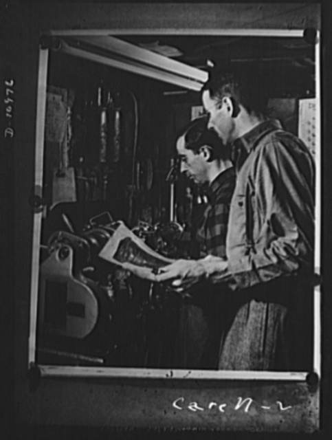 Conversion. From garage to defense workshop. Carell supervising the set-up of a lathe with turret attachment in the basement of his home where he does subcontracting on war work. His day shift consists of the expert mechanics