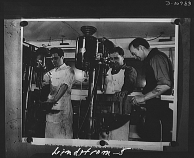Conversion. From garage to defense workshop.  Here he is shown supervising a drilling job. The drill jigs in which the parts are held were made and designed by Lindstrom