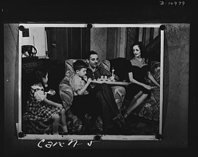 Conversion. From garage to defense workshop. In the living room of his home in suburban Passaic, New Jersey, Carell shows his son, George junior, a toy battleship as his wife and daughter look on. When mechanical work was just his hobby, he made his children a fine model railroad