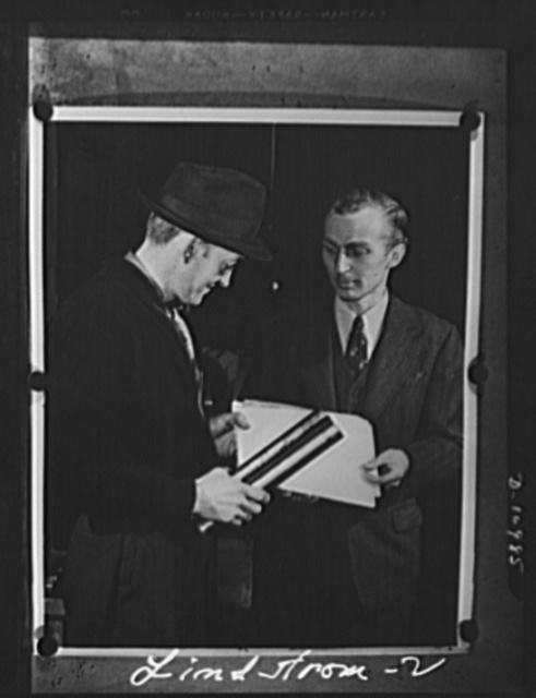 Conversion. From garage to defense workshop. John Lindstrom, right, is supplied with blueprints and raw materials by Albert Kuehn, general superintendent of the Howe Company. He will return the finished part for inspection when finished