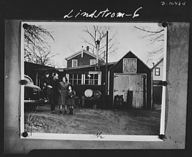 Conversion. From garage to defense workshop. Lindstrom put his car in the garage to make room for his shop in the garage. Above, he standss outside with his wife and town children, John, 10, and Nancey, 7. This is an outstanding example of the small man doing his bit in the nations's vast war effort