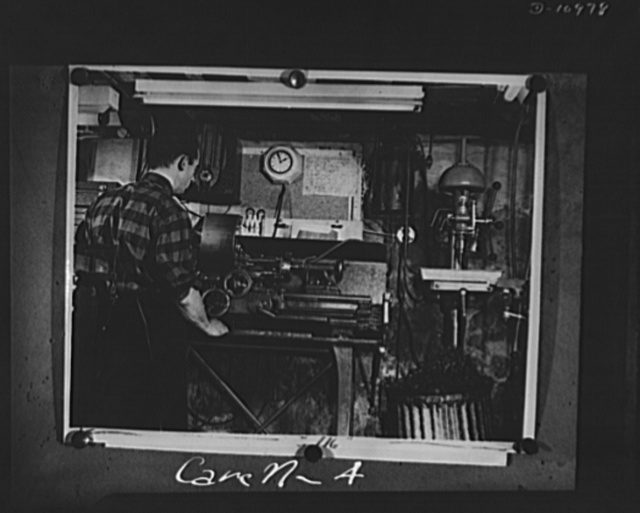 Conversion. From garage to defense workshop. One of Carell's workmen at a lathe in this basement war workshop. The lathe has a tailstock turret attachment which holds several tools so that one operation can follow another in quick succession, as in the factory production