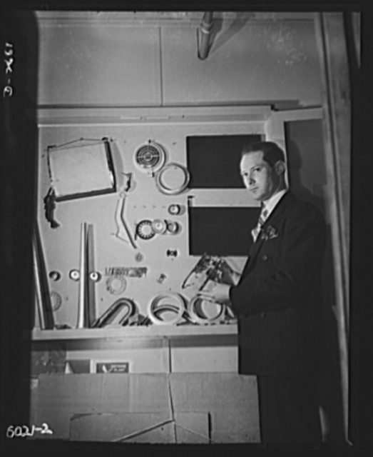 Conversion. Frying pans to aircraft parts. Peacetime production of this small Eastern manufacturing plant consisted of such objects as the aluminum photograph dryer (upper left), radio dials, and similar articles for civilian use. Its parts for America's fighting planes. Pictures above is one of the owners of the company. He's holding another peacetime product, a radio chassis