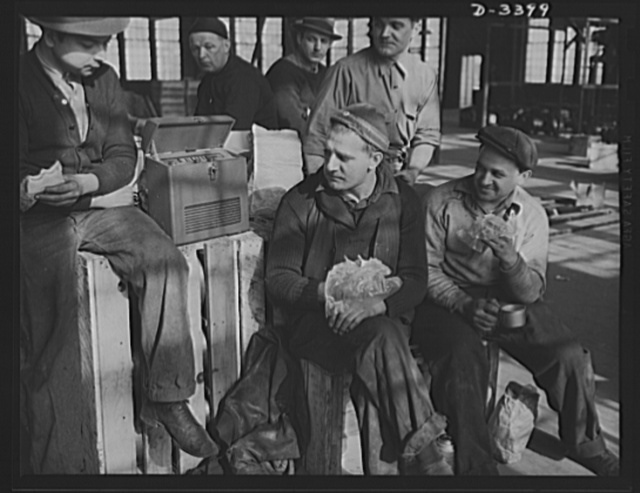 Conversion. Heaters to bogie wheels. How'd it go today with the boys at Bataan? These employees of a Midwest heater company take time out for lunch and the news before resuming work on installing assembly apparatus for M-4 tank bogie wheels in a company warehouse