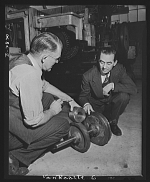 Conversion. Hosiery factory. These gears were once used in the manufacture of women's stockings. Today they've been put to far more important use with their conversion to the production of mosquito netting for America's armed forces. Here, two plant engineers inspect the worm gear changeover on a loom undergoing conversion. These gears are frequently known as mesh gears, since they control the size and type of the netting mesh. Van Raalte Company