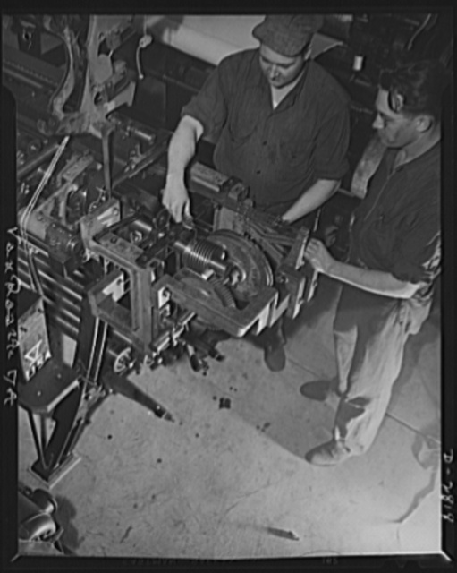 Conversion. Hosiery factory. These husky workers used to manufacture triple-sheer hosiery for Miss America. Today they're working for their Uncle Sam servicing mesh gears on a loom now producing mosquito netting for the Army and Navy. Van Raalte Company