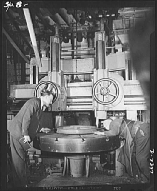 Conversion. Merry-go-round plant. These hands and this machine used to turn out merry-go-rounds to gladden the hearts of the nation's children. The carrousel plant in which they work is now engaged in producing war parts on subcontracts from army and navy contractors. While a plant officer looks on, machinist Arthur Greaces operates a Bickford vertical boring machine formerly used in the production of merry-go-rounds, now used for war work. He is machining a sheaf ordered as part of a sub-contract on maritime work. Spillman Engineering Company, North Tonawanda, New York