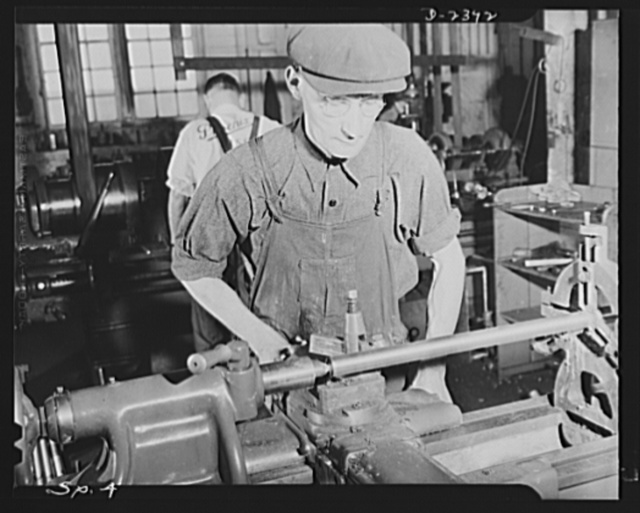 Conversion. Merry-go-round plant. These hands used to turn out merry-go-rounds to gladden the hearts of the nation's children. The carrousel plant in which they work is now engaged in producing war parts on subcontracts from army and navy contractors. Joe Wiegand is the machinist shown above, turning a rod for a shell extractor for a six-inch forty-seven-caliber naval gun. Spillman Engineering Company, North Tonawanda, New York