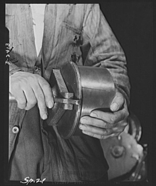 Conversion. Merry-go-round plant. These hands used to turn out merry-go-rounds to gladden the hearts of the nation's children. The carrousel plant in which they work is now engaged in producing war parts on subcontracts from army and navy contractors. Above is a completed shell ejector getting its final testing. The brass bottom of a navy shell is applied on the testing stand, with the spring mechanism which actually ejects the shell getting the primary test. Spillman Engineering Company, North Tonawanda, New York